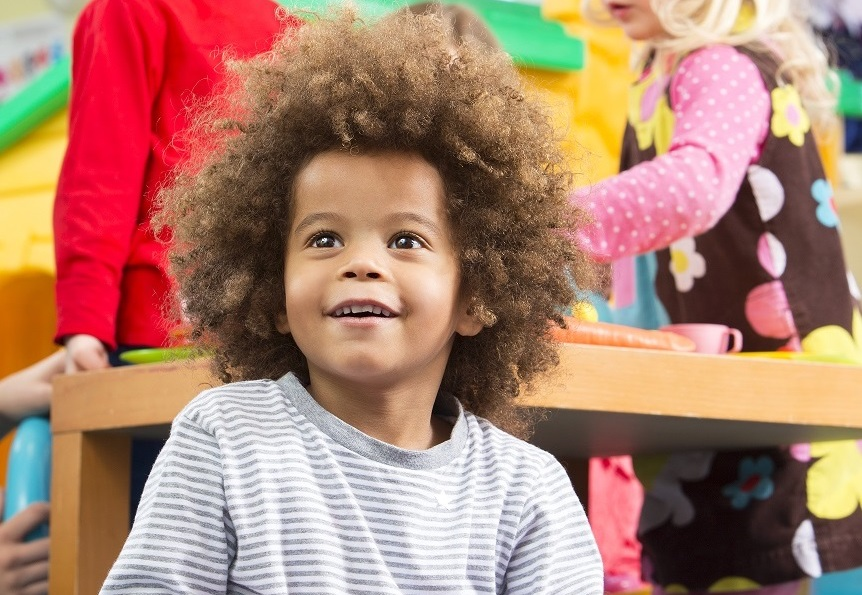The focus is on a little cute boy playing on the floor of the nursery, whilst other children are sat around a small table smiling and playing with a tea set. The little boy is mixed race and has an afro hairstyle, he looks very content and cheerful playing with a toy.