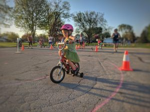 Young girl riding bike at the Safe Routes to School Family Fun Night Event in Neenah, Wisconsin in May 2018; orange cone in the background